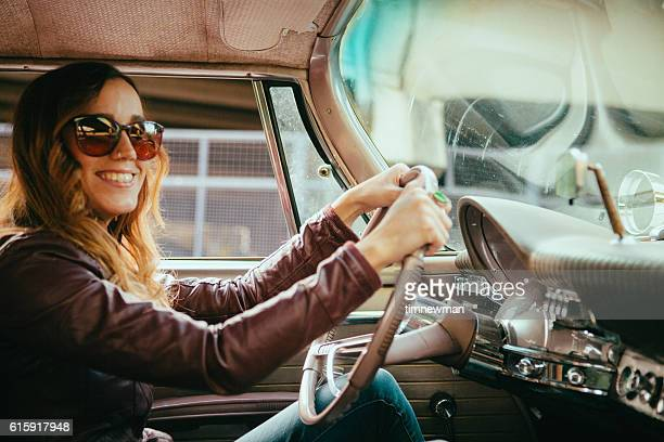 smiling young woman driving vintage american car - vintage car stock pictures, royalty-free photos & images