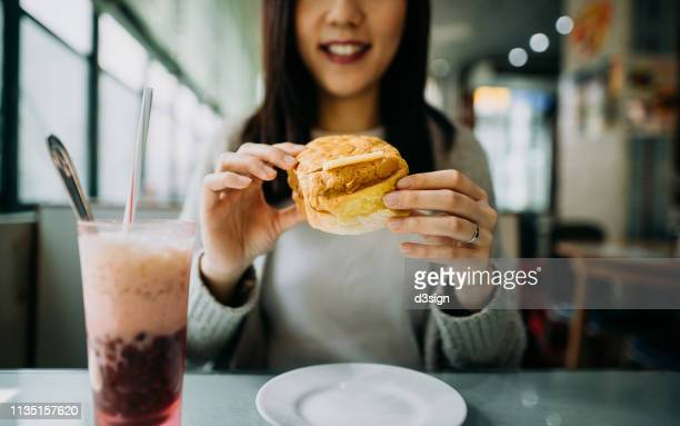 Smiling young woman eating Hong Kong style local foods, buttered pineapple bun with iced red bean drink in traditional restaurant