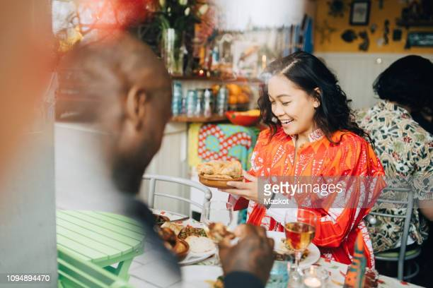 smiling young woman eating lunch with friend sitting at table in restaurant seen through window - brunch stock pictures, royalty-free photos & images