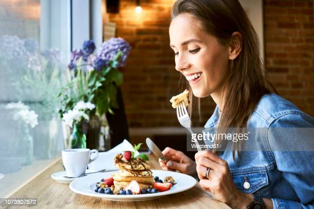 smiling young woman eating pancakes in cafe - pancakes stock pictures, royalty-free photos & images