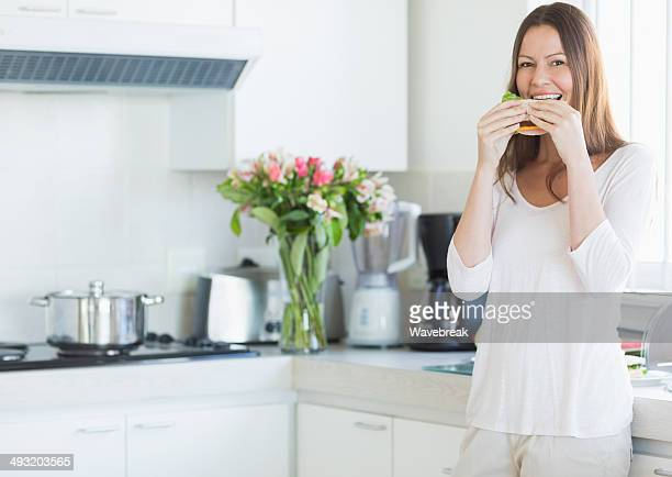 Smiling young woman eating sandwich in kitchen