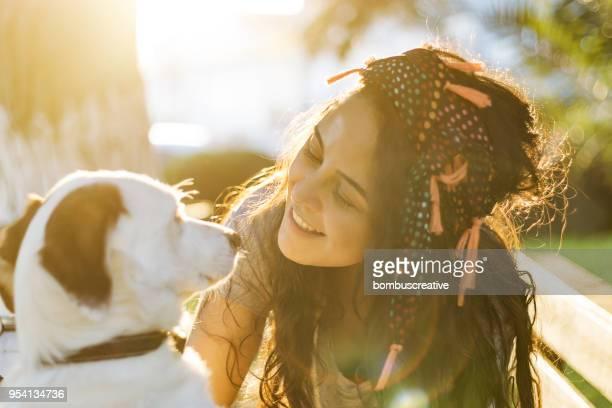 mulher jovem sorridente, abraçando um cão - respeito - fotografias e filmes do acervo
