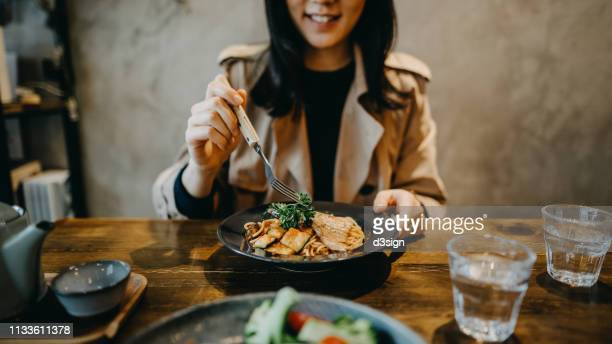 smiling young woman enjoying dinner date with friends in a restaurant - man eating woman out - fotografias e filmes do acervo