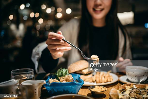 smiling young woman enjoying her meal and sharing her food in a restaurant - dîner photos et images de collection