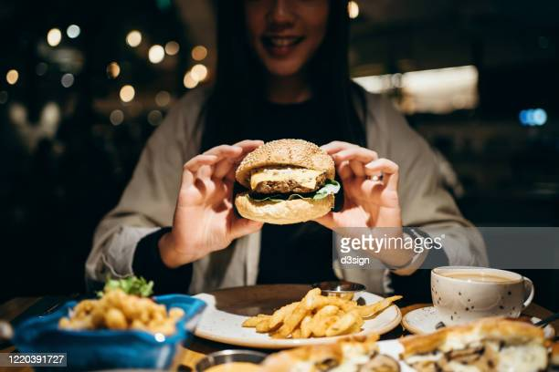 smiling young woman enjoying her meal in the restaurant, holding a burger and ready to bite into it - 食べ過ぎ ストックフォトと画像