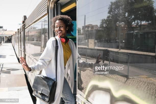 smiling young woman entering a train - eintreten stock-fotos und bilder