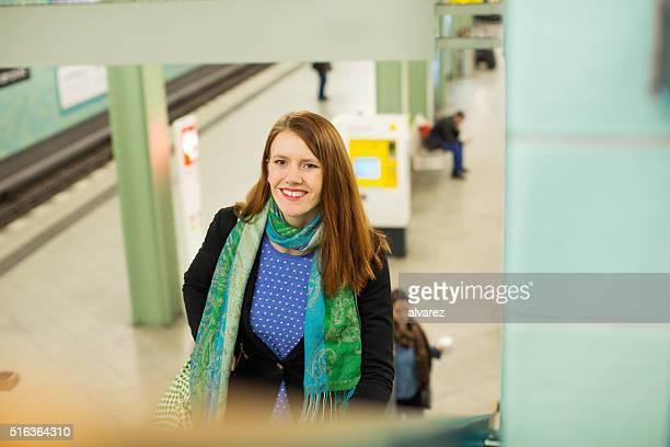 Souriante jeune femme en sortant de la station de métro