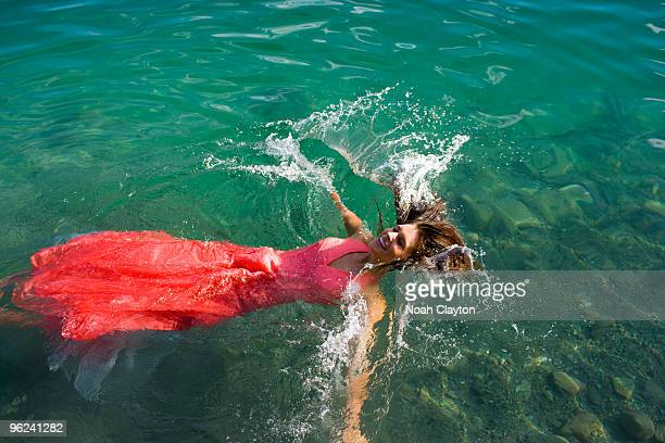 Smiling young woman falling into lake