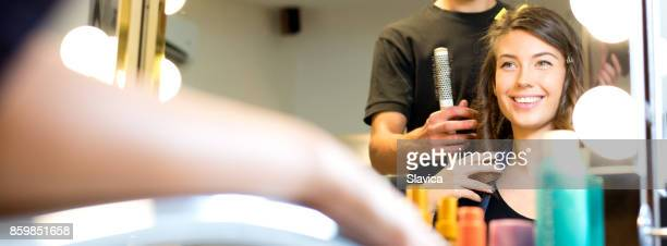 smiling young woman getting new hairstyle in the hair salon - beauty salon stock pictures, royalty-free photos & images