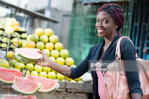 smiling young woman grabs a slice of ripe fruit in a street market. - femme ivoirienne photos et images de collection