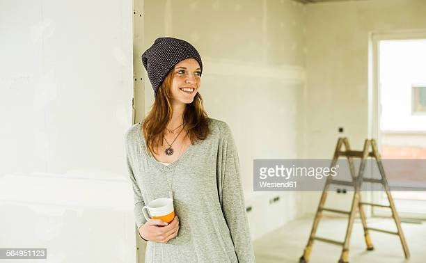 Smiling young woman having a coffee break from renovating