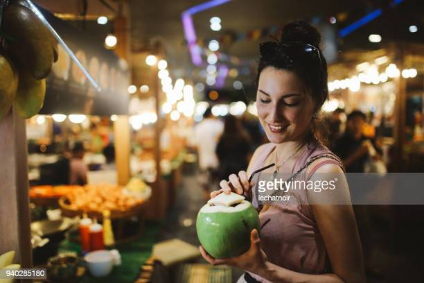 smiling young woman having a delicious and fresh coconut water on the go - street food stock pictures, royalty-free photos & images