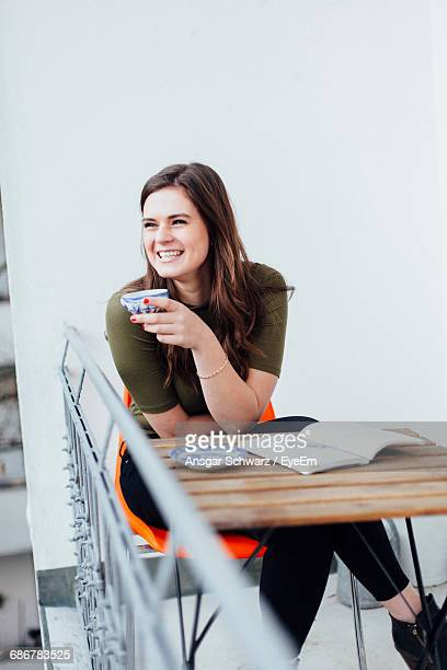 smiling young woman having coffee while sitting on chair at balcony - literature stock photos and pictures
