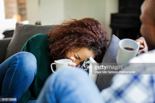 smiling young woman having coffee with man on sofa - woman sitting on man's lap stock pictures, royalty-free photos & images