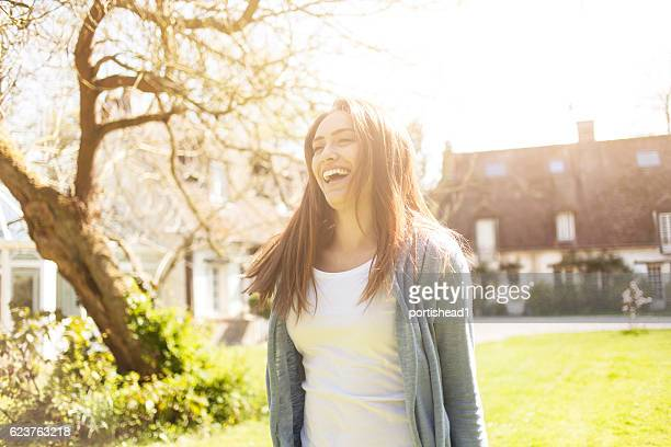 Smiling young woman having fun in front of a house
