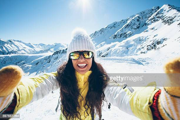 smiling young woman having fun in the snow mountain - wintersport stock-fotos und bilder