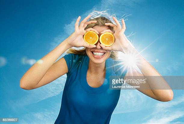 Smiling young woman hiding eyes with orange slices