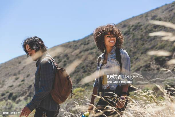 smiling young woman hiking with boyfriend on sunny day - diversity stock pictures, royalty-free photos & images