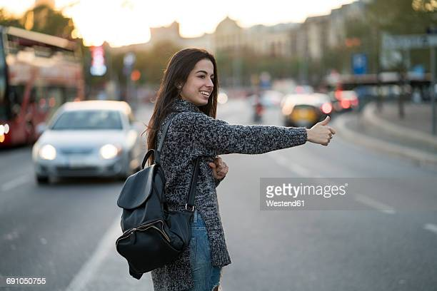 smiling young woman hitchhiking on urban street - hitchhiking stock pictures, royalty-free photos & images