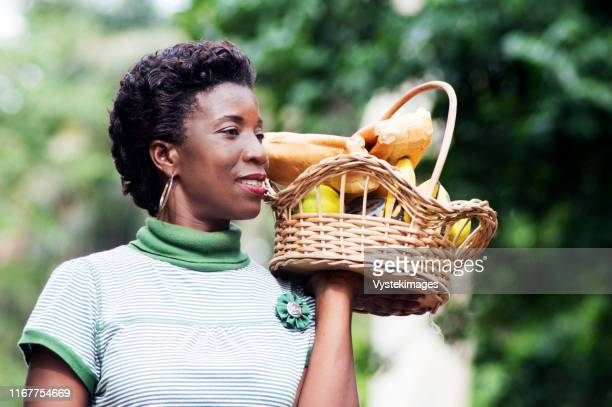 smiling young woman holding a basket of fruit in her hand and went for a picnic - côte d'ivoire stock pictures, royalty-free photos & images