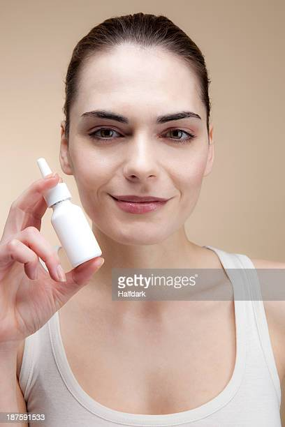 A smiling young woman holding a bottle of nasal spray