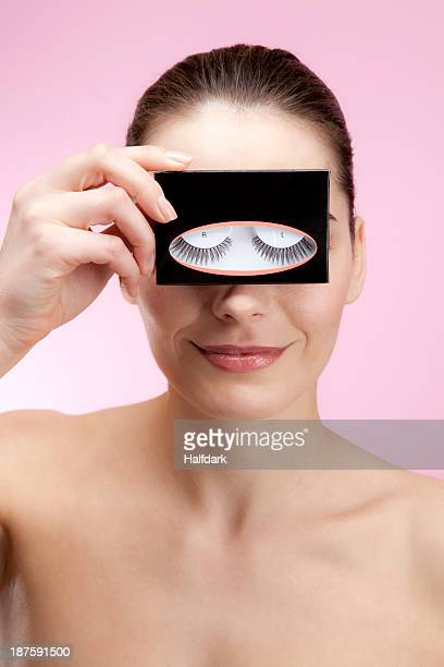 A smiling young woman holding a box of false eyelashes up to her eyes