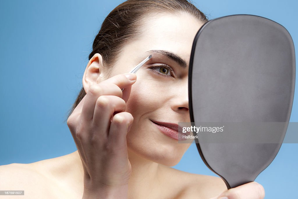 A smiling young woman holding a hand mirror and tweezing her brows : Stock Photo