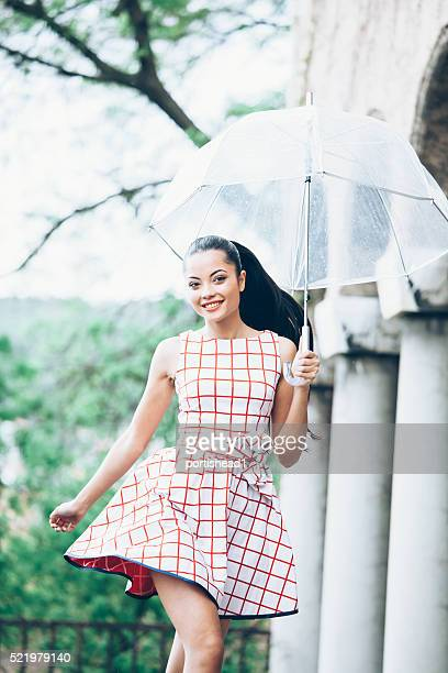 Smiling young woman holding an umbrella