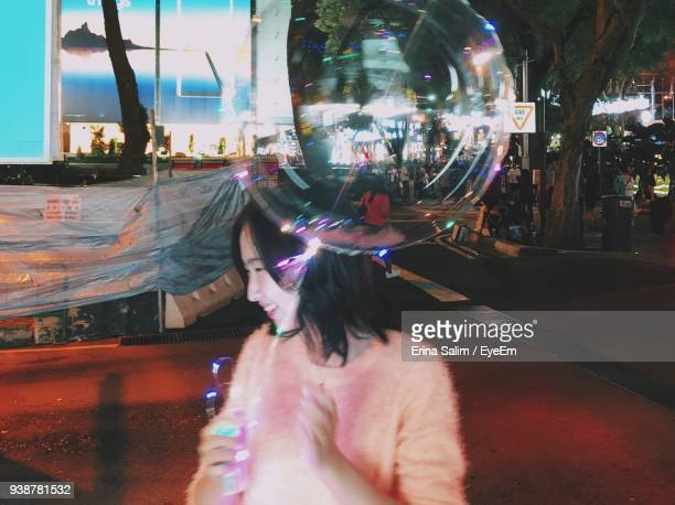 Smiling Young Woman Holding Balloon While Standing In City At Night