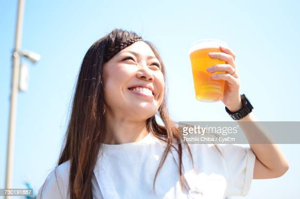 Smiling Young Woman Holding Beer Glass Against Clear Sky On Sunny Day