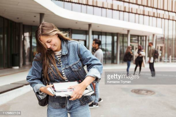 smiling young woman holding books while standing in university campus - campus photos et images de collection