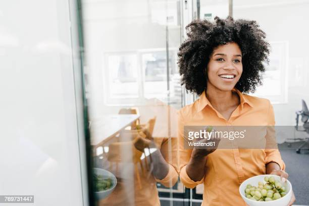 Smiling young woman holding bowl with grapes in office