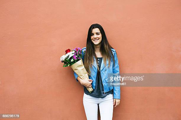Smiling young woman holding bunch of flowers
