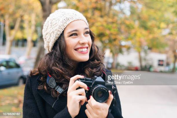 Smiling Young Woman Holding Camera In City During Winter