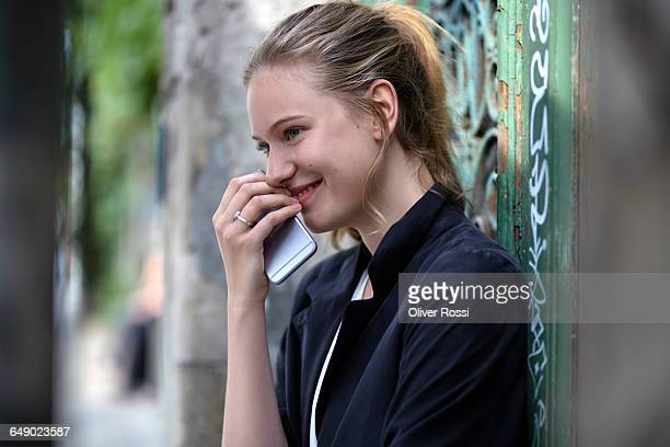 Smiling young woman holding cell phone outdoors