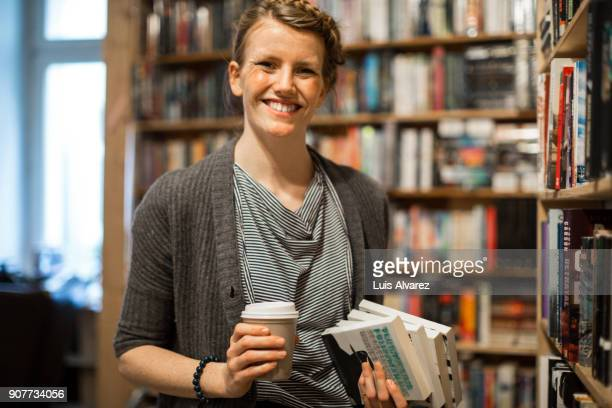 Smiling young woman holding coffee cup and books