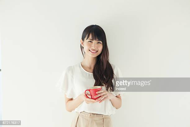 smiling young woman holding coffee cup - 20代 ストックフォトと画像