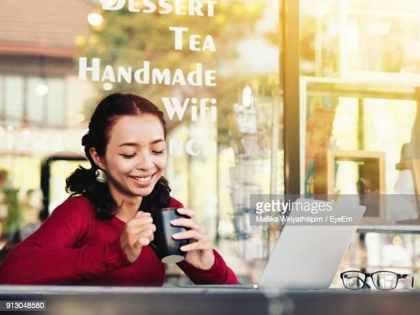 Smiling Young Woman Holding Coffee Cup With Laptop On Table At Cafe