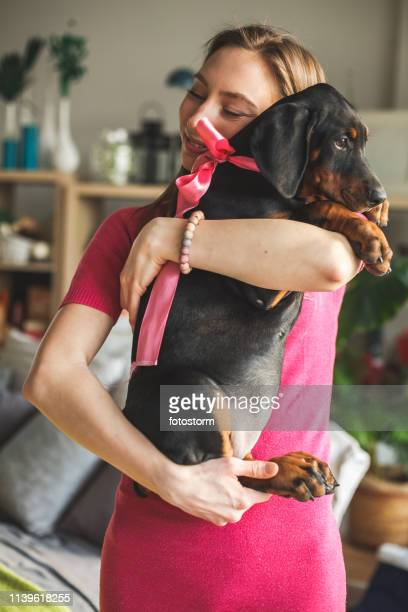 smiling young woman holding doberman puppy - dog knotted in woman stock pictures, royalty-free photos & images
