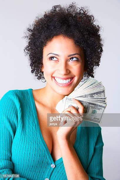 smiling young woman holding dollar bills in her hand