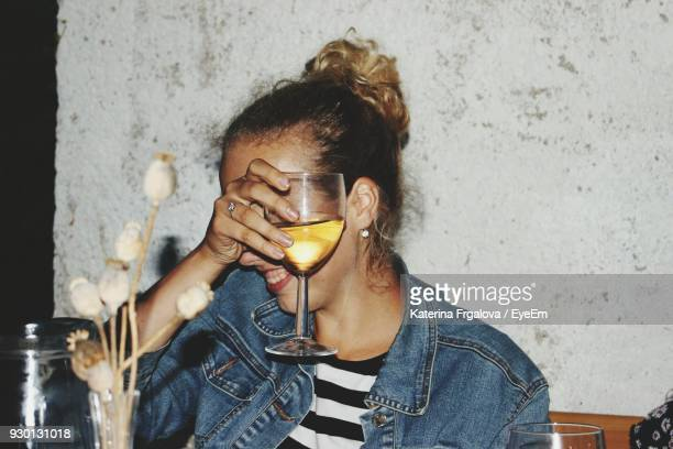 Smiling Young Woman Holding Glass In Restaurant