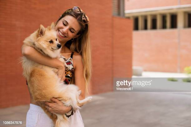 smiling young woman holding her dog - one animal stock pictures, royalty-free photos & images