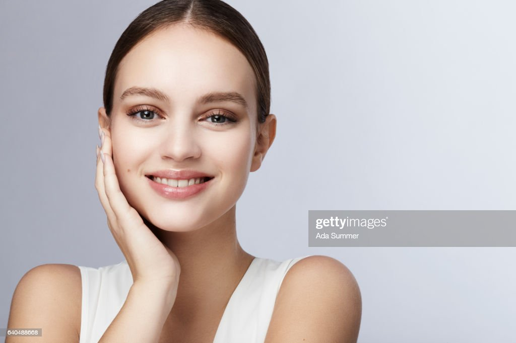 smiling young woman holding her face with her hand : ストックフォト