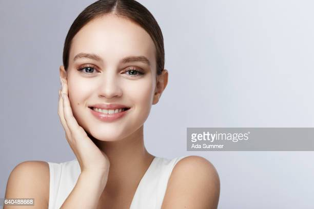 smiling young woman holding her face with her hand