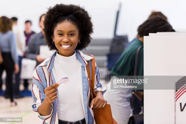 "smiling young woman holding ""i voted"" sticker at voting place - voting stock pictures, royalty-free photos & images"