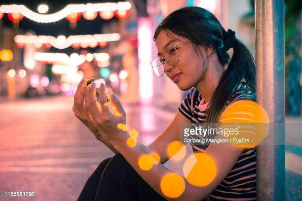 Smiling Young Woman Holding Illuminated String Lights While Sitting On Street At Night