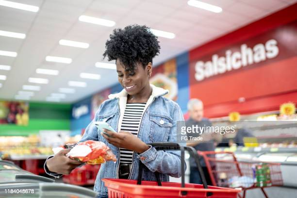 smiling young woman holding product in supermarket and searching on the phone - market retail space stock pictures, royalty-free photos & images