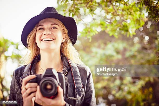 Smiling young woman holding SLR Camera while looking away