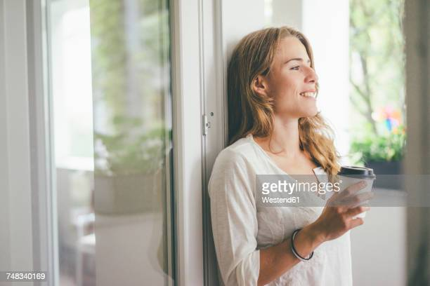 smiling young woman holding takeaway coffee at the window - gelassene person stock-fotos und bilder