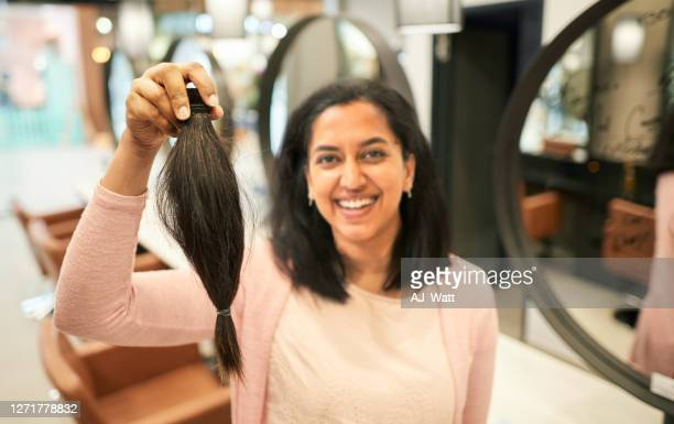 smiling young woman holding up her cut ponytail in a salon - ponytail stock pictures, royalty-free photos & images